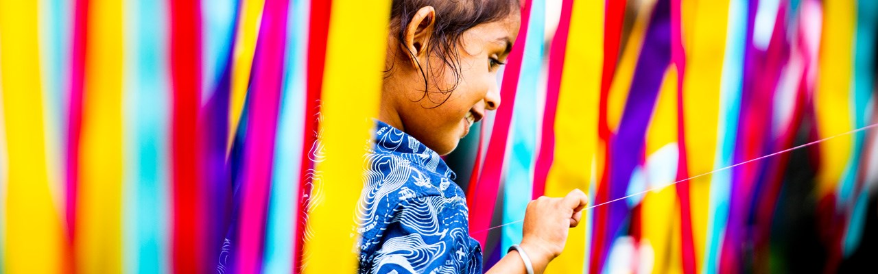 Kid playing with colourful ribbons